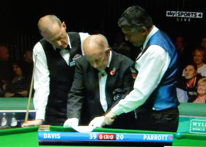 Parrott, trapped in a snooker, misses it twice, not realising that in this tournament, three consecutive misses means ball in hand for the opponent. The game stops for a few minutes while referee John Williams confirms the rule.